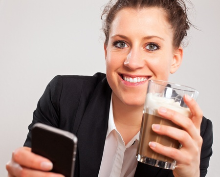 Closeup portrait of an office girl with a  phone and coffee in hand enjoying her break photo