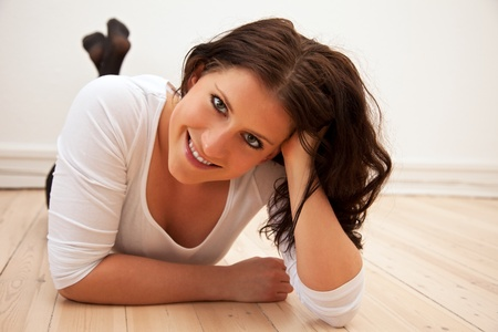 Portrait of a smiling confident woman lying on the floor photo