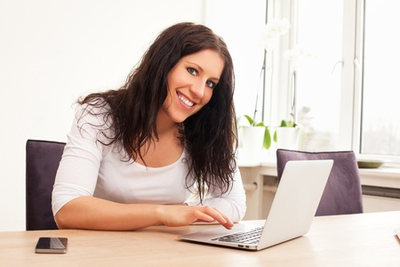 Portrait of a smiling woman browsing the Internet using a laptop photo