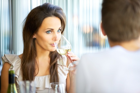 date: Portrait of an attractive woman drinking wine while on a date with her boyfriend Stock Photo