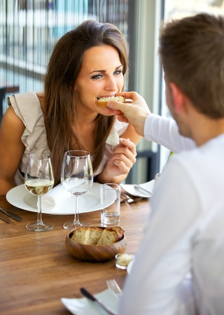 Portrait of a man feeding bread to his girlfriend photo
