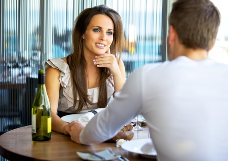 Portrait of a gorgeous woman holding hands with her boyfriend at a fancy restaurant Stock Photo