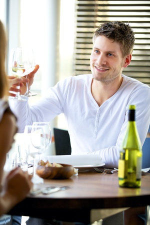 couple dining: Portait of a man toasting with a glass of wine at a restaurant Stock Photo
