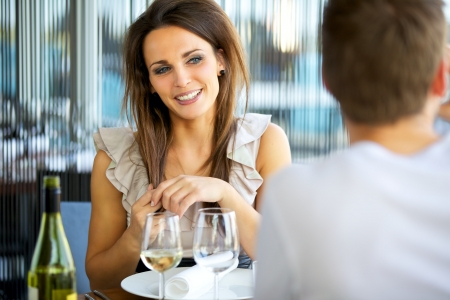 flirting: Portrait of a gorgeous woman smiling at her date while holding her hair