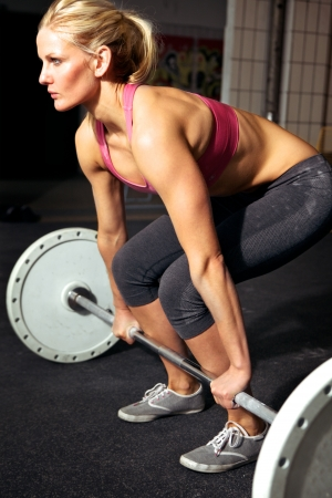 barbell: Young female doing a workout with weights in her local gym
