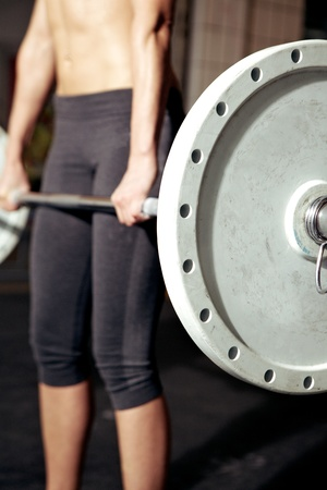 heavy lifting: Closeup of heavy weight bar with woman performing deadlift in background