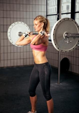 lifting: Portret van een sexy fitness vrouw optillen van een gewicht Stockfoto