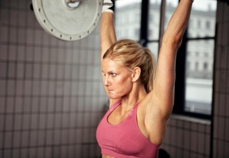 lifting: Fitness vrouw zich te concentreren op het tillen van zware gewicht in de gymzaal Stockfoto