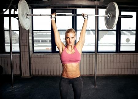 levantando pesas: Mujer atractiva forma de realizar un ejercicio de press de hombros