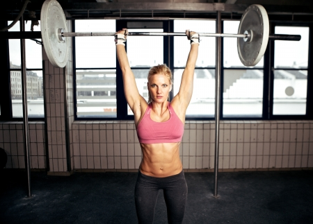 heavy lifting: Sexy fit woman performing a shoulder press exercise