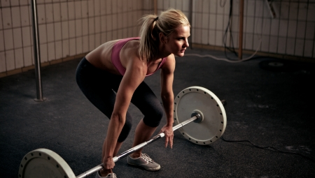 Woman preparing herself for a heavy lift inside gym photo