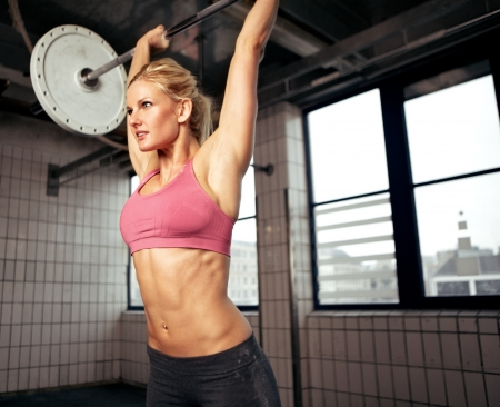 Woman doing shoulder press exercise with a weight bar inside a gym photo