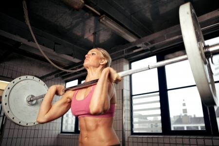 Bodybuilder doing exercise with a heavy weight bar inside gym photo