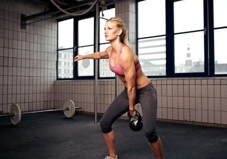 crossfit: Young adult fitness woman doing swing exercise with a kettlebell as a part of a crossfit workout