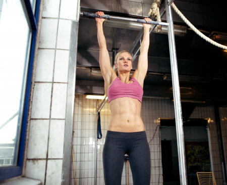 ups: Young adult fitness woman preparing to do pull ups in pull up bar.