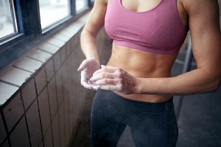 Woman in sportswear chalking her hands before lifting a weight Stock Photo - 14158007