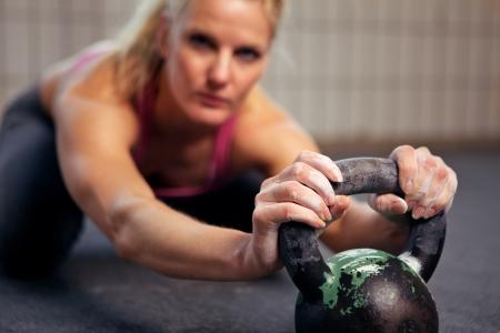 kettles: Retrato de mujer joven que tiene un breve descanso en su entrenamiento crossfit kettlebell Foto de archivo