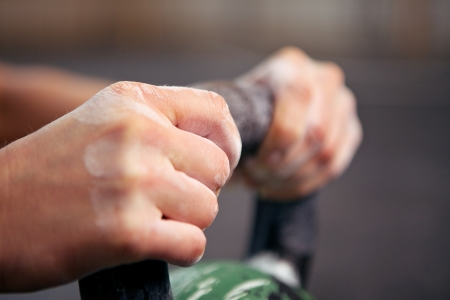 kettles: Closeup picture of two handings grabbing a kettlebell Stock Photo