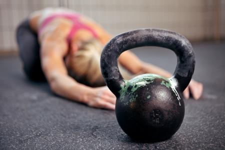 kettles: Joven mujer se extiende la espalda después de una fuerte sesión de ejercicios en un gimnasio de pesas rusas