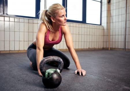 Portrait of a beautiful woman resting during her crossfit exercise with a kettlebell
