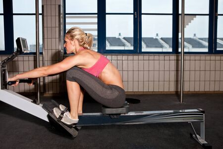 exercise machine: Young fit woman rowing indoor on a rowing machine Stock Photo