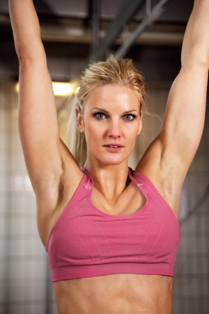 Portrait of beautiful fitness woman hanging in pull up bar photo