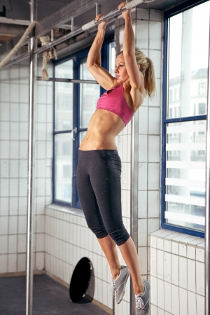 pulling beautiful: Sexy fit woman performing pull ups in a bar