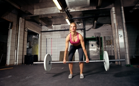 Female crossfit performing doing deadlift exercise with weight bar Stock Photo