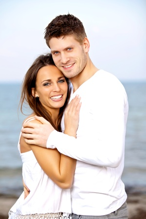 couple embracing: Portrait of a smiling couple posing with the beach as background