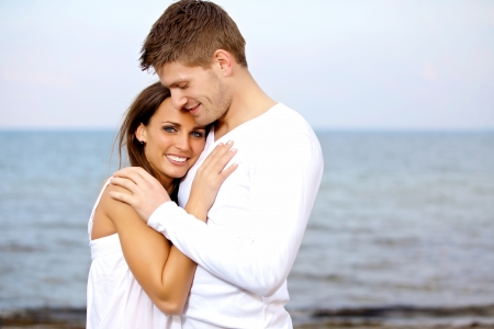 embrace: Portrait of a couple cuddling at the beach looking happy