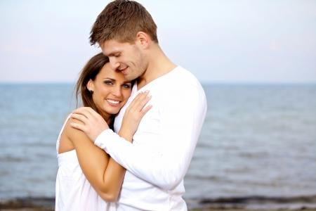 personas abrazadas: Retrato de una pareja de mimos en la playa con una mirada feliz Foto de archivo