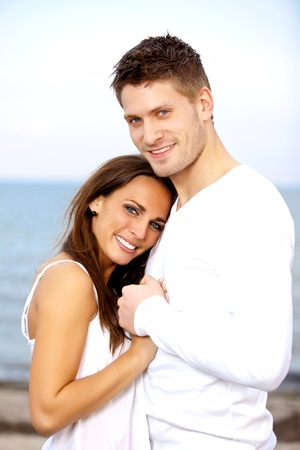 Portrait of a happy couple holding each others hands posing with the sea as a background photo