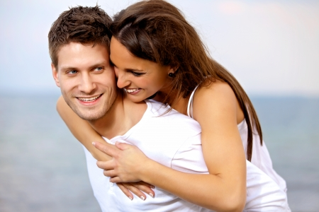 piggyback ride: Portrait of a handsome man piggybacking his girlfriend on a vacation Stock Photo