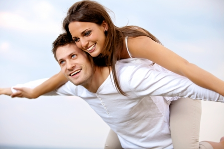 Portrait of a happy young couple enjoying each others company with the nice summer sky as background photo