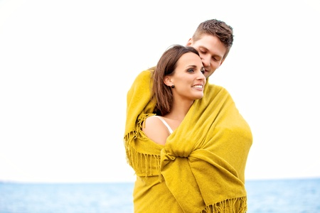 Portrait of a romantic couple embracing while wrapped with a blanket photo