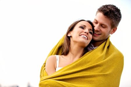 personas abrazadas: Retrato de una pareja romántica con una manta que parece feliz aislado en blanco Foto de archivo