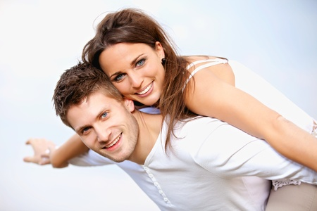 young couple smiling: Portrait of a happy young couple enjoying their summer vacation, isolated on bright background Stock Photo