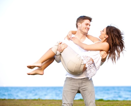 man carrying: Portrait of a guy carrying his beautiful girlfriend in a windy beach Stock Photo