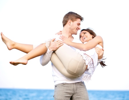 men and women: Portrait of a romantic guy looking affectionately at his girlfriend while carrying her