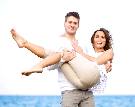 carrying girlfriend: Portrait of an attractive couple in a windy beach posing against a white background Stock Photo