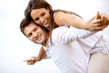 carrying girlfriend: Portrait of a happy young couple having fun against a bright background Stock Photo