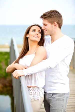 Portrait of a romantic young couple looking at each other while dating outdoors photo