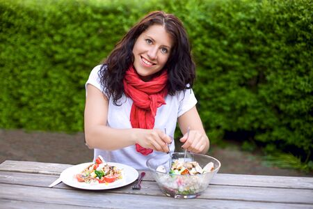 Portrait of a woman smiling while preparing a bowl of salad outdoors photo