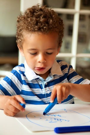 crayon drawing: Portrait of a adorable little boy drawing something on paper