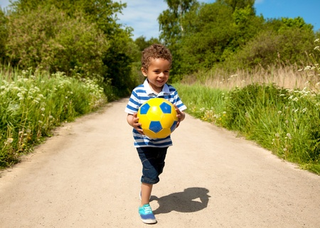 niño corriendo: Niño jugando con una pelota al aire libre en un día caluroso Foto de archivo