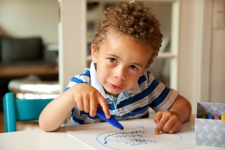 scribbling: Charming toddler busy doing his art activity at his desk
