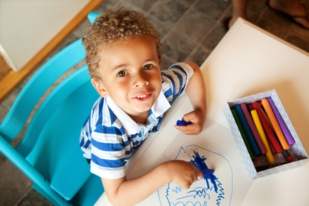 toddler playing: Charming Little Kid Looking Up and Playing with Crayons Stock Photo