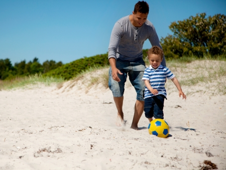 Father and son enjoying a soccer game on the beach photo