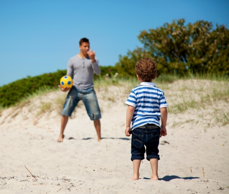 Child looking at his dad teaching him how to play soccer outdoors photo