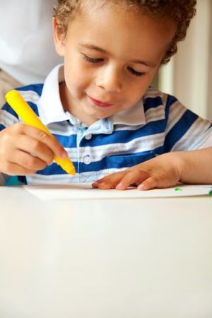 art activity: Young happy boy busy doing his art activity indoors Stock Photo